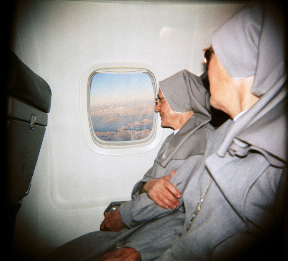 Christopher Anderson. Nuns looking out the window at the Alps below on a flight from Italy to Switzerland. 2003