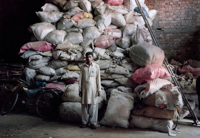 Valentino Bellini. Lahore, Pakistan. A guy stands in front of a huge pile of electronic components which will later be processed to extract precious metals.